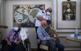 A man receives his second Pfizer-BioNTech COVID-19 vaccine from a Magen David Adom national emergency service volunteer, at a private nursing home in Ramat Gan, on January 13, 2021. (AP Photo/Oded Balilty)