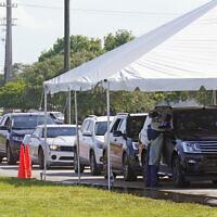 Cars line up at Miami Dade College North campus' COVID-19 testing site, July 29, 2021, in Miami (AP Photo/Marta Lavandier)