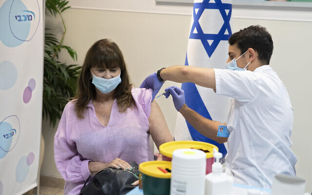 An Israel woman receives a third Pfizer-BioNTech COVID-19 vaccine in the central city of Ramat Hasharon, July 30, 2021. (AP Photo/Sebastian Scheiner)