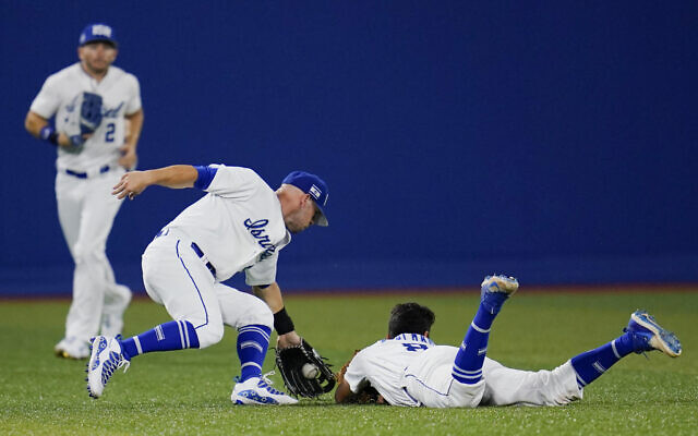 Israel's Scott Burcham, right, dives and cannot reach a ball picked up by Rob Paller, center, as Blake Gailen (2) looks on during a baseball game against the United States at the 2020 Summer Olympics on July 30, 2021, in Yokohama, Japan. (AP/Sue Ogrocki)