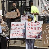 People from a coalition of housing justice groups hold signs protesting evictions during a news conference outside the Statehouse, July 30, 2021, in Boston. (AP Photo/Michael Dwyer)