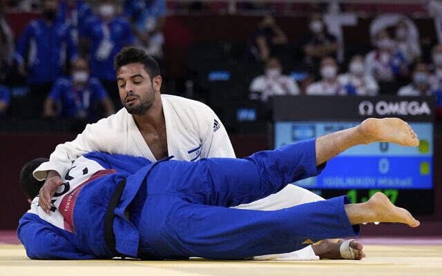 Sagi Muki of Israel, top, and Mikhail Igolnikov of the Russian Olympic Committee compete during their bronze medal match in team judo competition at the 2020 Summer Olympics, on July 31, 2021, in Tokyo, Japan. (AP Photo/Vincent Thian)