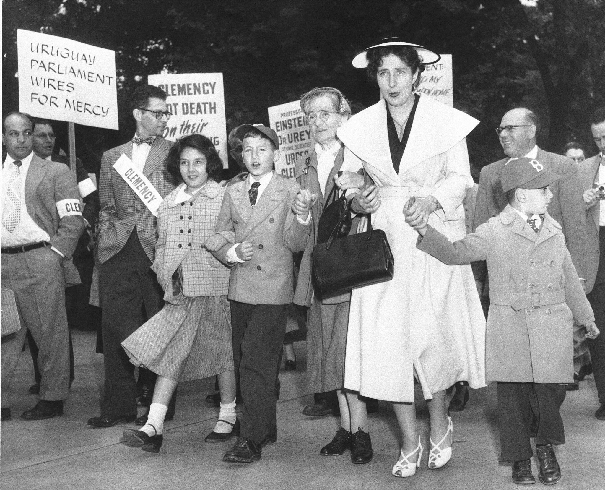 The two sons of condemned spies Julius and Ethel Rosenberg and Julius' mother join marchers in front of the White House during a demonstration by persons seeking clemency for the Rosenbergs in Washington, June 14, 1953. Michael, 10, walks between his grandmother, Sophie Rosenberg, and an unidentified girl. Robert, 6, looks away at right as his hand is held by Emily Alman, a leader of the demonstration. Others are unidentified. (AP Photo/Bob Schutz)