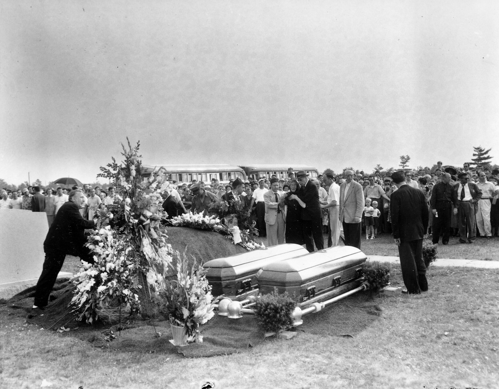 Defense attorney Emanuel Bloch, in dark suit, comforts Sophie Rosenberg as she views the caskets of her son and daughter-in-law, executed spies Julius and Ethel Rosenberg, during the funeral service at Wellwood Cemetery at Pine Lawn, Long Island, New York, on June 21, 1953. (AP Photo)