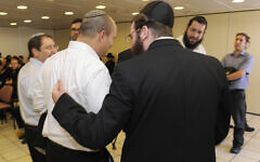 An ultra-Orthodox Jewish man speaks with then-Economy Minister Naftali Bennett following a discussion about drafting ultra-Orthodox men to service in the Israeli army in the Yad Sara building in Jerusalem, on June 11, 2013. (Zuzana Janku/Flash 90)