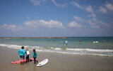 Illustrative -- Young children learning to surf at a beach in Tel Aviv, on a hot summer day, July 30, 2018 (Miriam Alster/FLASH90)