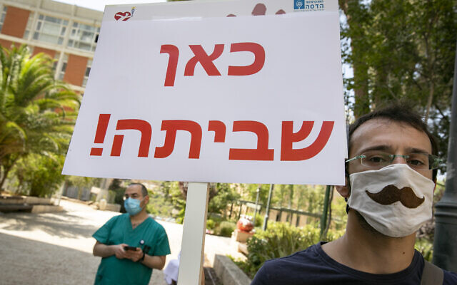 """Illustrative: A man with a sign reading """"strike here!"""" takes part in a strike of nurses at Hadassah Hospital in Jerusalem on July 20, 2020. (Olivier Fitoussi/Flash90)"""