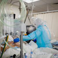 Shaare Zedek Medical Center staff wearing protective clothes move patients to the new Coronavirus ward of the hospital in Jerusalem, on January 7, 2021. (Olivier Fitoussi/Flash90)