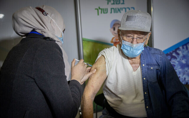 A man receives a COVID-19 vaccine shot at a vaccination center in Jerusalem on January 21, 2021. (Yonatan Sindel/Flash90)
