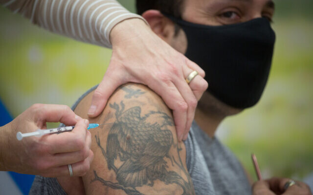 Israelis recieve a Covid-19 vaccine, at a sports hall turned into a Clalit Health vaccination center in Hod HaSharon, February 02, 2021. (Miriam Alster/Flash90)