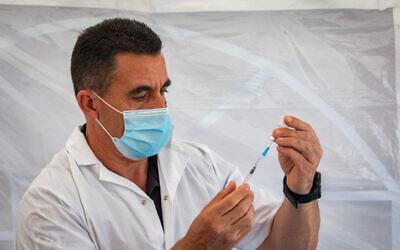 An Israeli medical worker prepares a coronavirus vaccine (Olivier Fitoussi/Flash90)