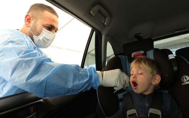 Healthcare worker takes a COVID-19 test sample in Netanya, on April 13, 2021 (Chen Leopold/Flash90)