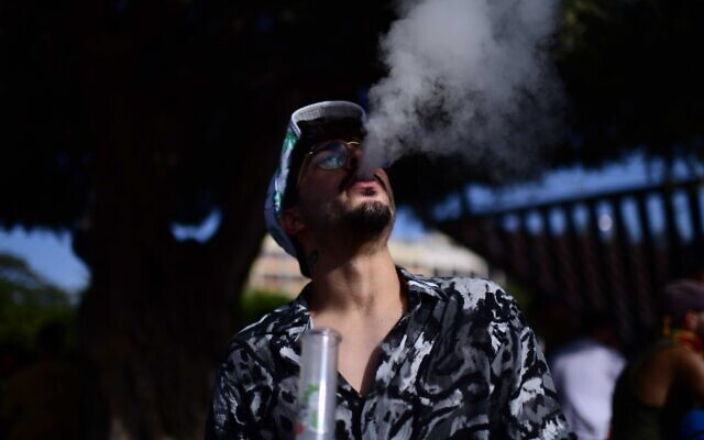 An Israeli man smokes marijuana at Rabin Square in Tel Aviv during a demonstration calling to legalize cannabis, on April 20, 2021. (Tomer Neuberg/Flash90)
