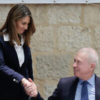 New Education Minister Yifat Shasha-Biton (L) shakes hands with outgoing Minister Yoav Gallant during a handover ceremony at the Education Ministry in Jerusalem, June 14, 2021. (Olivier Fitoussi/Flash90)