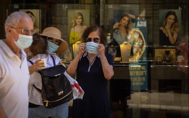 People walk face masks in Jerusalem on June 27, 2021. (Olivier Fitoussi/Flash90)