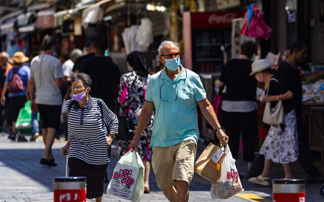 People walk some with face masks in Jerusalem on July 4, 2021. (Olivier Fitoussi/Flash90)
