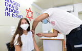 An Israeli girl receives a COVID-19 vaccine at a vaccination center in Tel Aviv, on July 4, 2021. (Tomer Neuberg/Flash90)