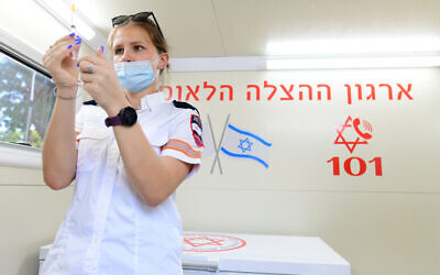 A health worker prepares a vaccination against COVID-19 at a vaccination center of the Tel Aviv municipality and Magen David Adom, in Tel Aviv, July 4, 2021. (Tomer Neuberg/Flash90)