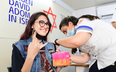 An Israeli teenager receives the COVID-19 vaccine at a vaccination center of the Tel Aviv municipality and Magen David Adom, in Tel Aviv on July 4, 2021. (Tomer Neuberg/Flash90)
