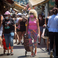 Israelis wear protective face masks as they walk through the Carmel market in Tel Aviv, on July 5, 2021. (Miriam Alster/FLASH90)