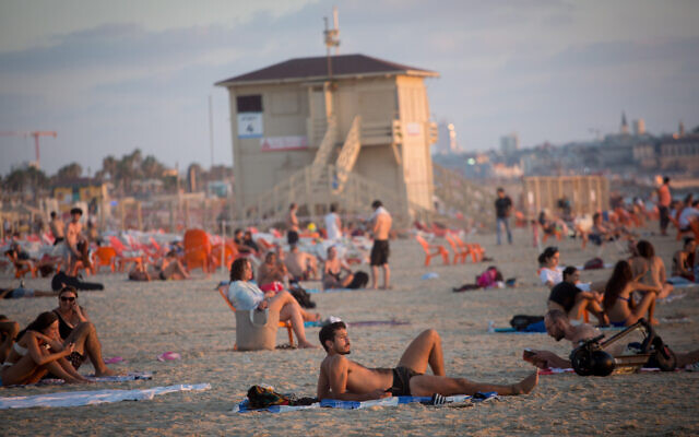Israelis enjoy the beach in Tel Aviv on a hot summer day, on July 6, 2021. (Miriam Alster/Flash90)