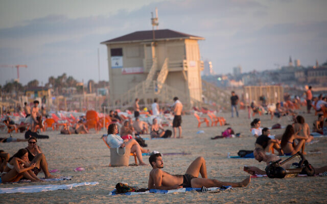 Israelis enjoy the beach in Tel Aviv, on a hot summer day on July 6, 2021. (Miriam Alster/FLASH90)