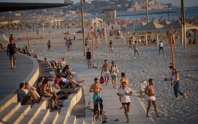 Illustrative: Israelis enjoy the beach in Tel Aviv on a hot summer day, on July 6, 2021. (Miriam Alster/Flash90)