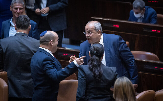 Prime Minister Naftali Bennett (L) speaks with Joint List MK Ahmad Tibi after a Knesset vote rejected an extension of the Palestinian family reunification law, in Jerusalem, July 6, 2021. (Yonatan Sindel/Flash90)