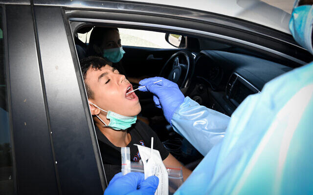 Israeli medical workers test for COVID at a drive-in testing compound in the Golan Heights. July 7, 2021. (Michael Giladi/Flash90)