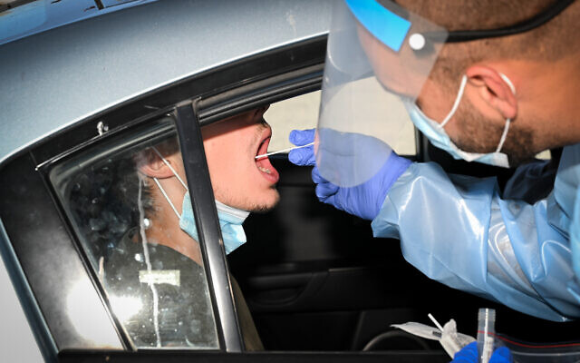 A medical worker test Israelis for COVID-19 virus at a drive-thru testing facility in the Golan Heights, on July 7, 2021. (Michael Giladi/Flash90)