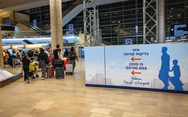 Travelers arriving at the Ben Gurion International Airport, stand in line to get a COVID-19 check upon arrival. July 1, 2021. (Nati Shohat/FLASH90)