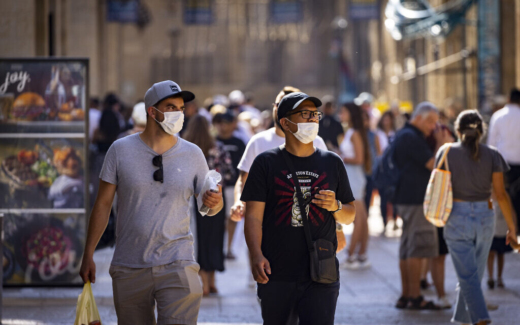 People, some wearing face masks, walk in Jerusalem on July 8, 2021. (Olivier Fitoussi/Flash90)