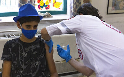 Child receives a COVID-19 vaccine injection in Jerusalem, July 8, 2021 (Olivier Fitoussi/Flash90)