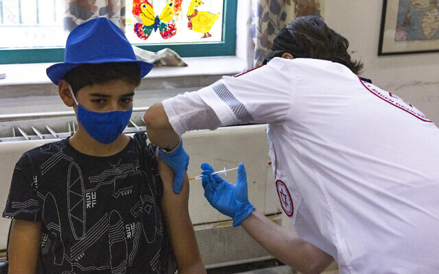 An Israeli youth receives the COVID-19 vaccine at a vaccination center of  Magen David Adom in Jerusalem on July 8, 2021. (Olivier Fitoussi/Flash90)