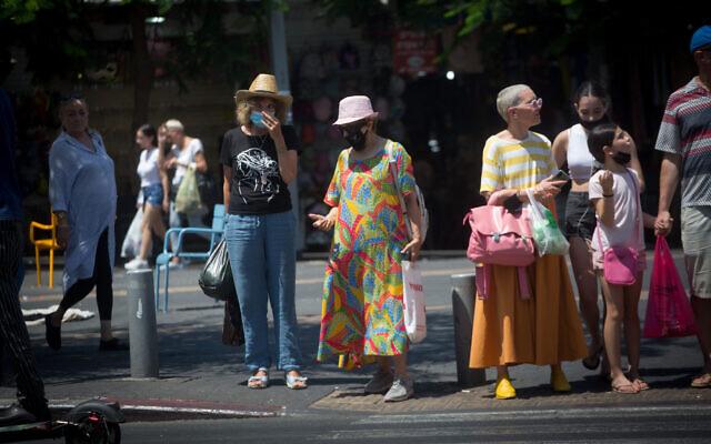 Israelis, some wearing face masks, walk in Tel Aviv on July 11, 2021. (Miriam Alster/Flash90)