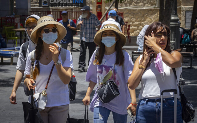 People, some with face masks, walk in Jerusalem on July 12, 2021. (Olivier Fitoussi/Flash90)