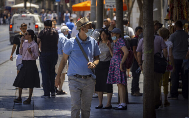 People, some wearing face masks, walk in Jerusalem on July 12, 2021. (Olivier Fitoussi/Flash90)