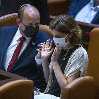 Prime Minister Naftali Bennett, left, speaks with Environmental Protection Minister Tamar Zandberg  in the assembly hall of the Knesset, on July 12, 2021. (Olivier Fitoussi/Flash90)