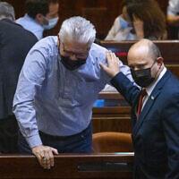Prime Minister Naftali Bennett (R) and Yisrael Beytenu MK Eli Avidar attend a plenum session in the Knesset, on July 12, 2021. (Olivier Fitoussi/Flash90)