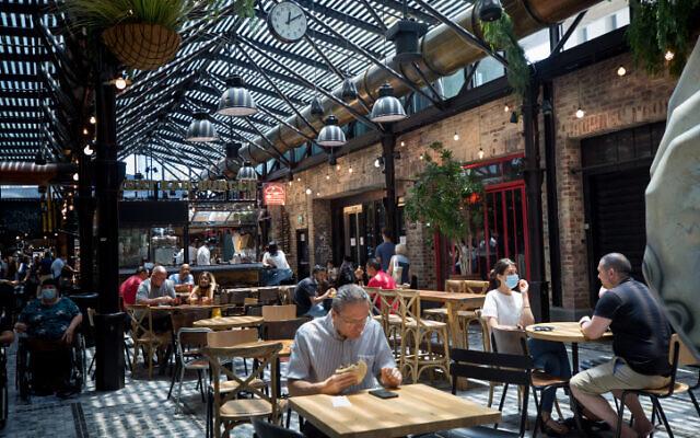People eating at Sarona market in Tel Aviv on July 13, 2021. (Miriam Alster/FLASH90)