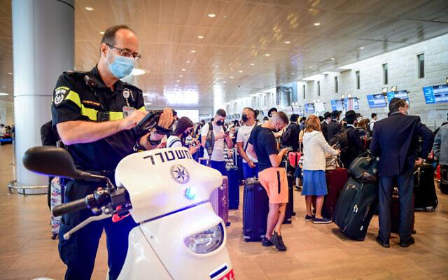 A police officer enforces COVID-19 regulations at Ben Gurion International Airport on July 19, 2021. (Avshalom Sassoni/Flash90)