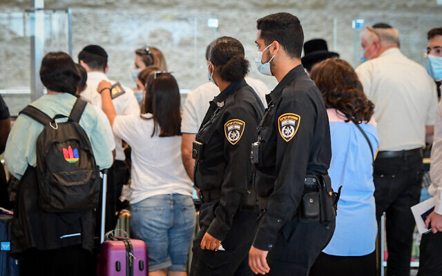 Police officers enforce COVID-19 regulations at Ben Gurion International Airport, on July 19, 2021. (Avshalom Sassoni/Flash90)