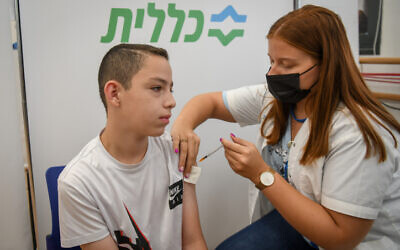 A young Israeli receives a COVID-19 vaccine in Petah Tikva, July 19, 2021. (Flash90)