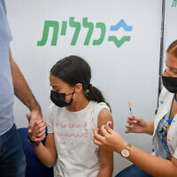 An Israeli youth receives a COVID-19 vaccine shot at a vaccination center in Petah Tikva, July 19, 2021. (Flash90)