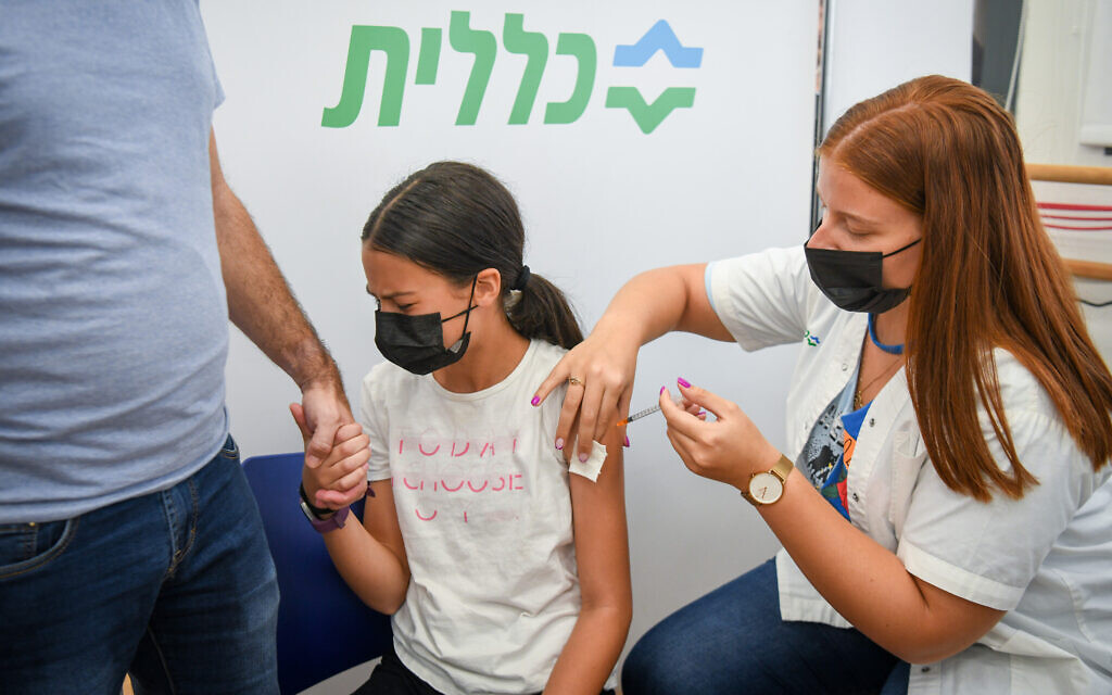 A young Israeli receives a coronavirus vaccine shot at a Clalit vaccination center in Petah Tikva, July 19, 2021. (Flash90)