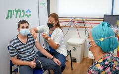 An Israeli youth receives the coronavirus vaccine in Petah Tikva, on July 19, 2021. (Flash90)