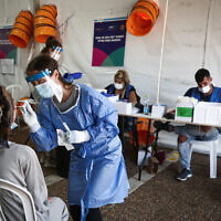 A technician collects nasal swab samples for COVID-19, at a testing center on Rabin Square in Tel Aviv, on July 20, 2021. (Miriam Alster/Flash90)