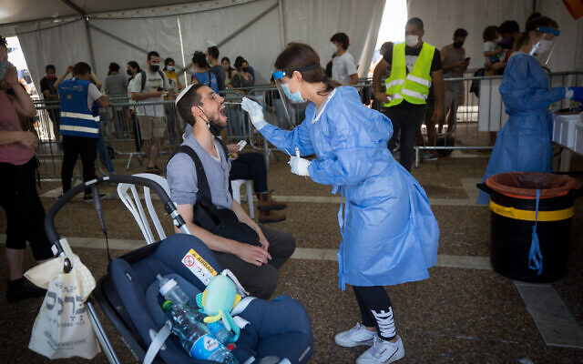 A technician collects swab samples for COVID-19 at a testing center run by the Tel Aviv Municipality at Rabin Square in Tel Aviv on July 20, 2021. (Miriam Alster/ Flash90)