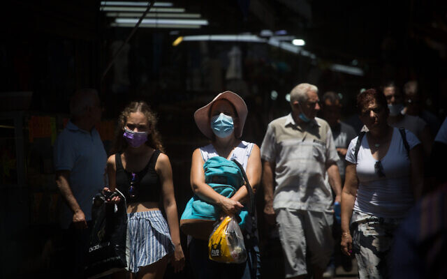 Israelis, some wearing face masks, as they walk through the Carmel Market in Tel Aviv on July 20, 2021. (Miriam Alster/Flash90)