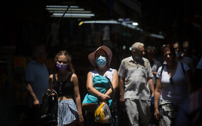 Israelis wear protective face masks as they walk through the Carmel market in Tel Aviv, on July 20, 2021. (Miriam Alster/FLASH90)